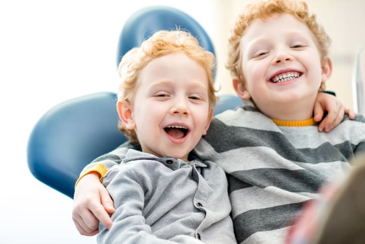 Portrait of a happy young brothers sitting on the dental chair at the dental office