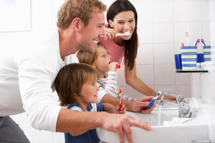 Family In Bathroom Brushing Teeth Together