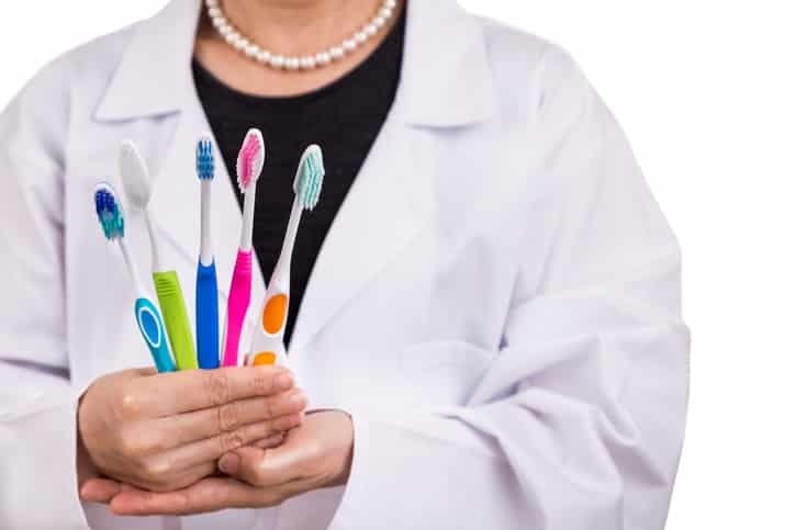 Dentist holding toothbrushes with different head and bristle design for various oral needs